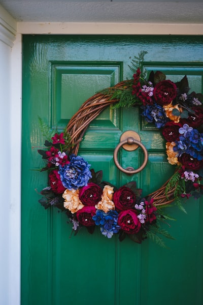 brown and red wreath on green wooden door