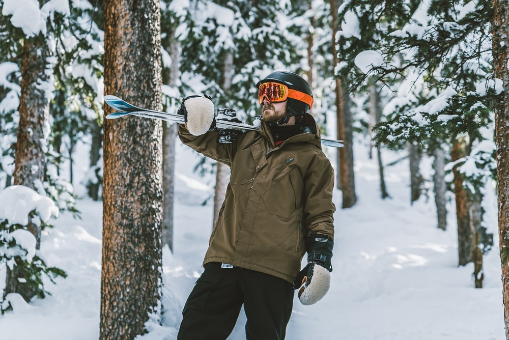 man in brown jacket and black pants holding black and white snow ski pole