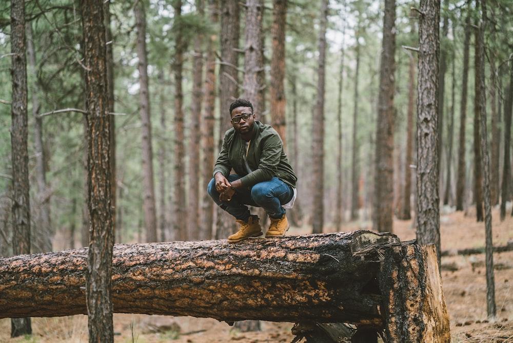 man in black jacket sitting on brown log during daytime