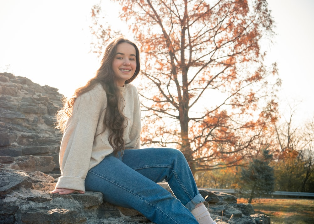 woman in white long sleeve shirt and blue denim jeans sitting on rock