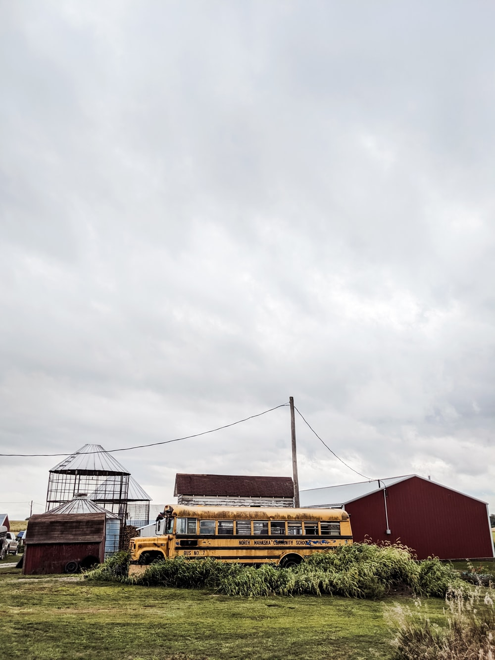 yellow and black bus on road under white clouds during daytime