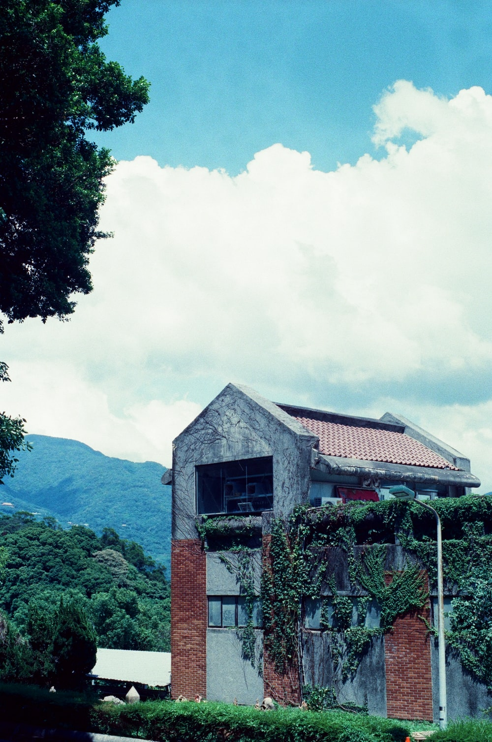 brown and white concrete house near green trees under white clouds and blue sky during daytime