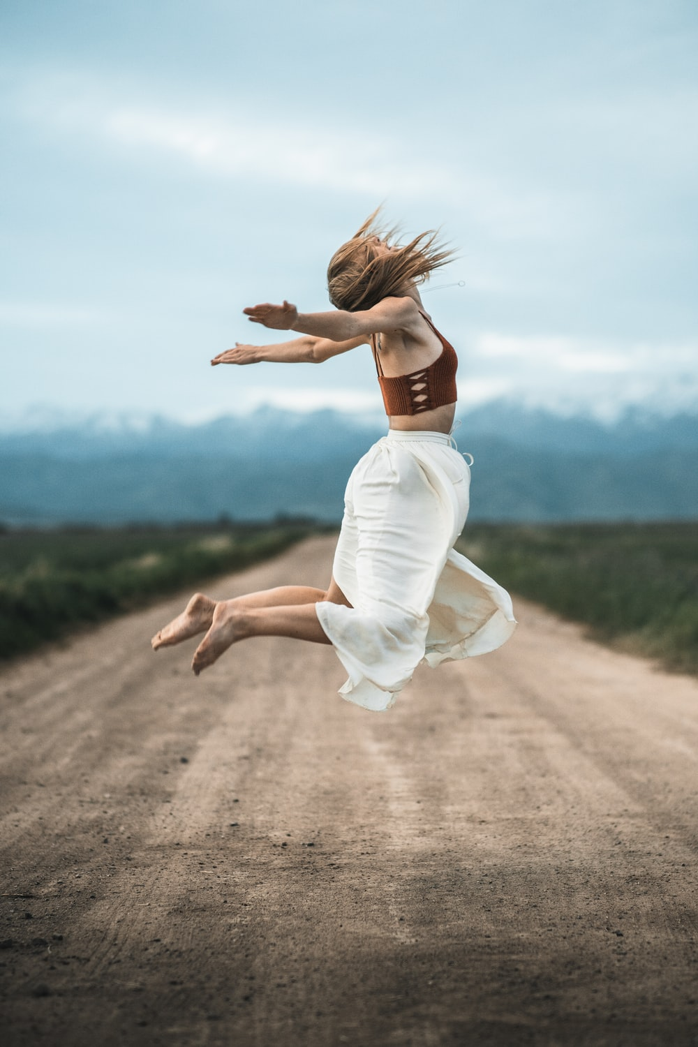 woman in white dress running on brown dirt road during daytime