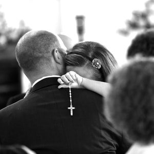 man in black suit kissing woman in black and white photo