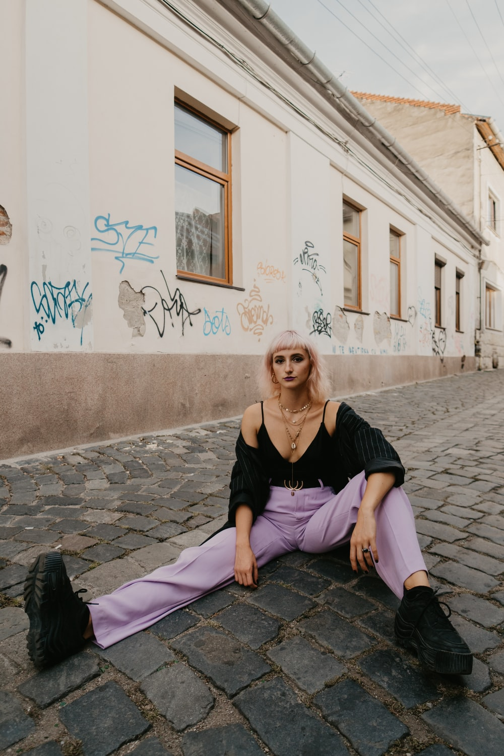 woman in black tank top and purple pants sitting on gray concrete floor