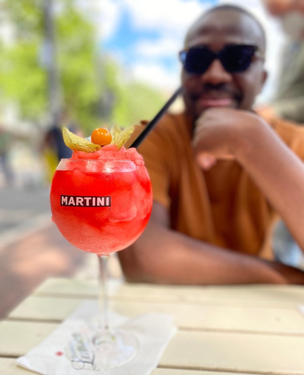 man in black sunglasses holding red fruit