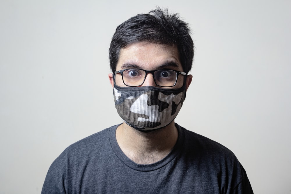man in black crew neck shirt wearing black and white mask