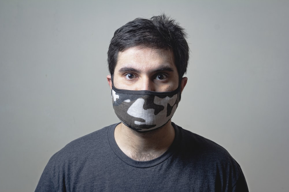 man in black crew neck shirt wearing black and white mask