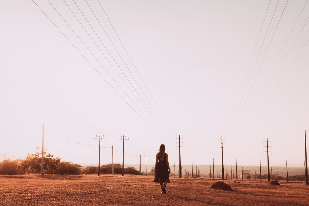 person in black jacket walking on brown field during daytime