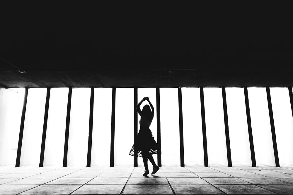 silhouette of woman walking on wooden floor