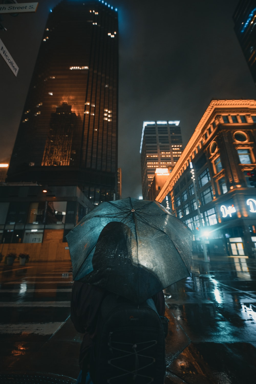 black umbrella near brown building during night time