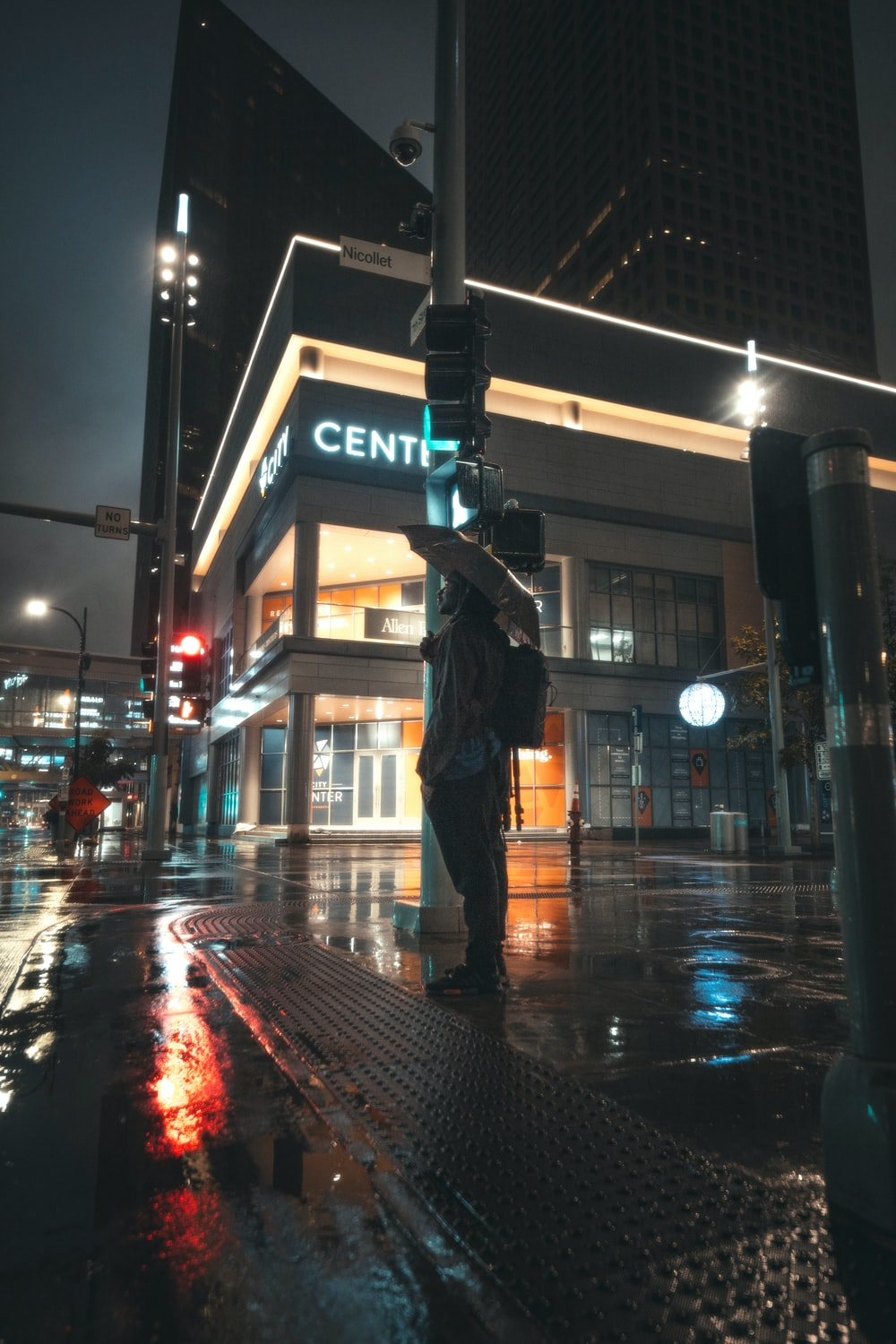 man in black jacket and black pants standing on street during night time
