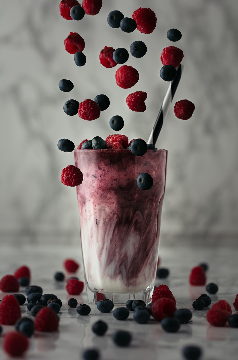 pink ice cream with red and blue berries on top