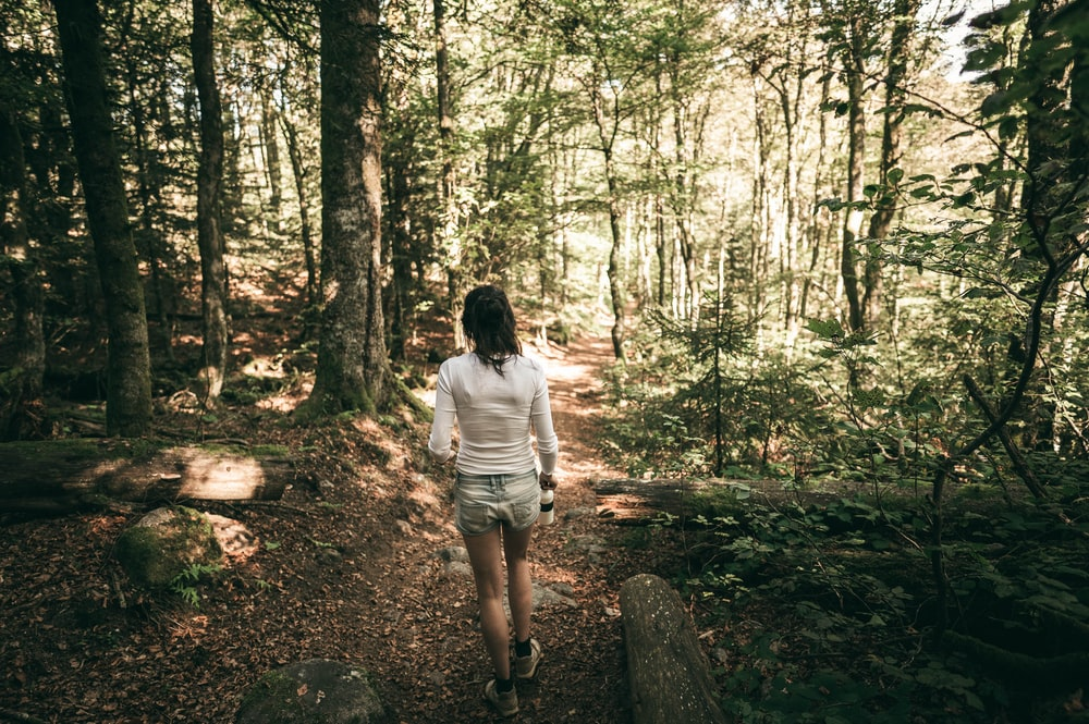 woman in white t-shirt and white shorts standing in the middle of forest during daytime