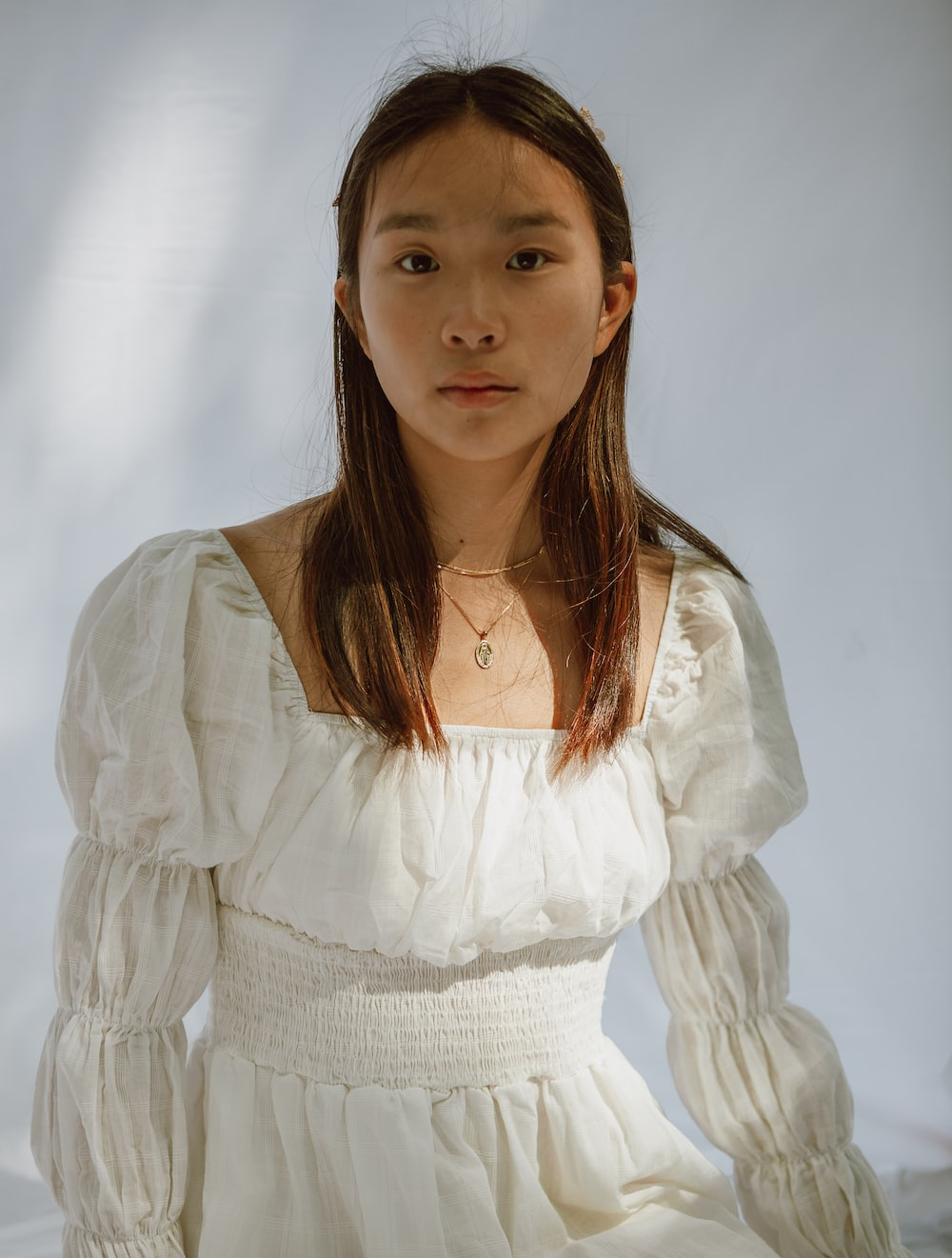 girl in white dress wearing silver necklace