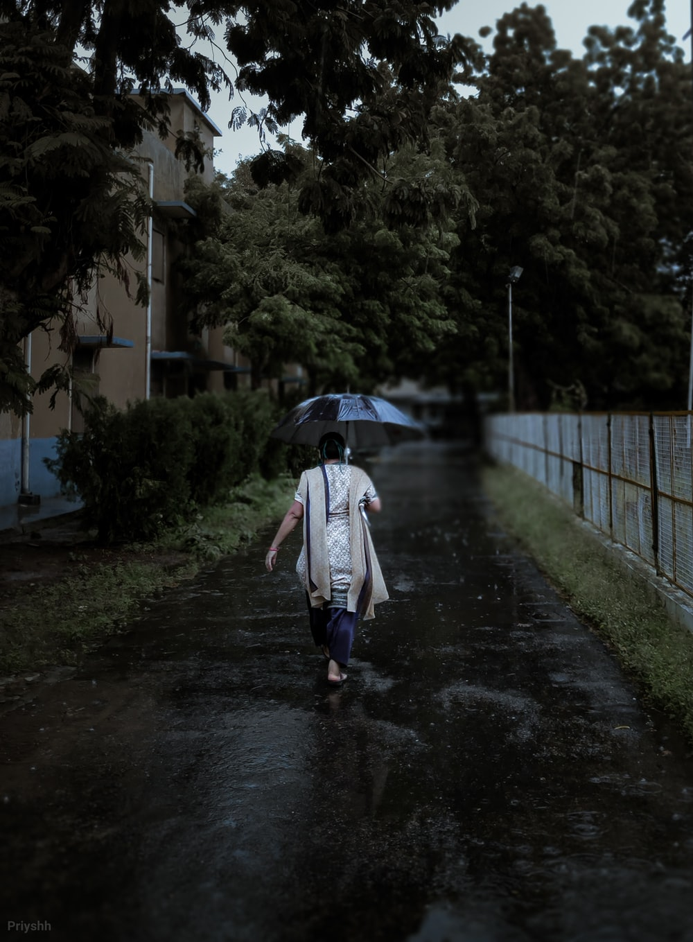 woman in white coat walking on pathway