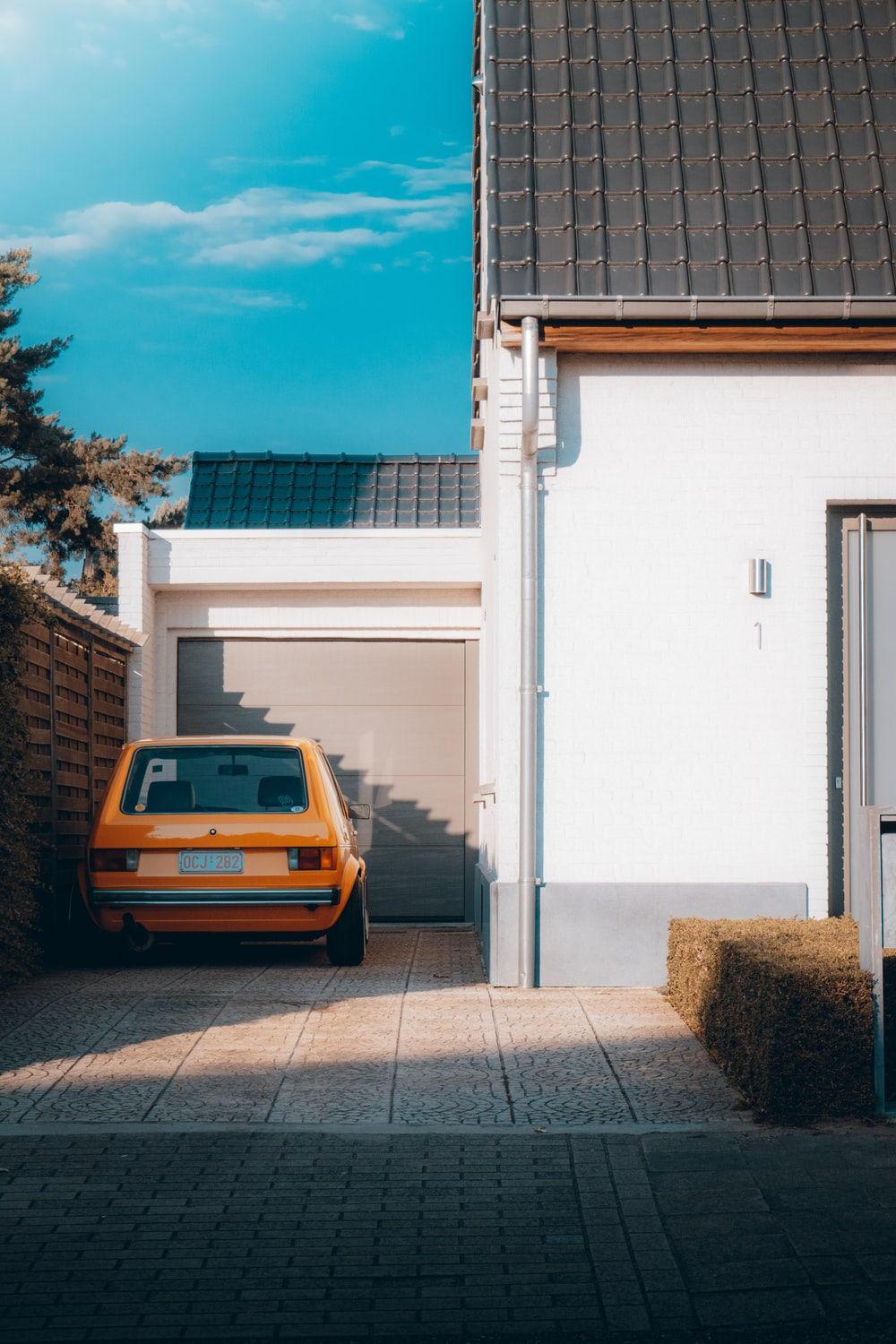 yellow car parked beside white building