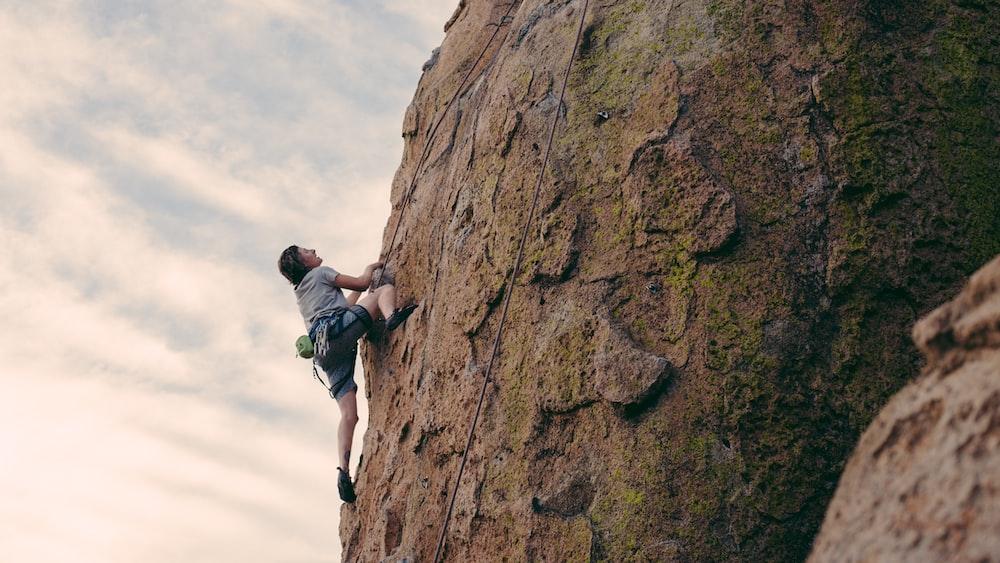 man in black t-shirt climbing on brown rock during daytime