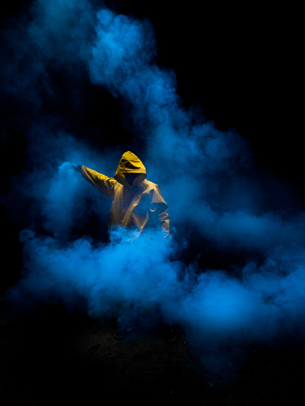 man in yellow hoodie and blue denim jeans standing on blue smoke