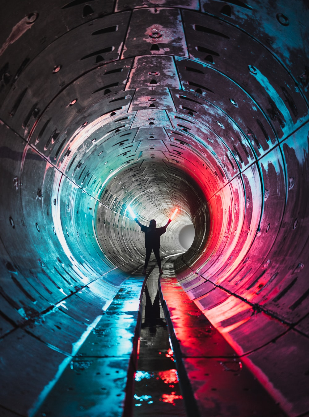 man in blue shirt and black pants standing on tunnel