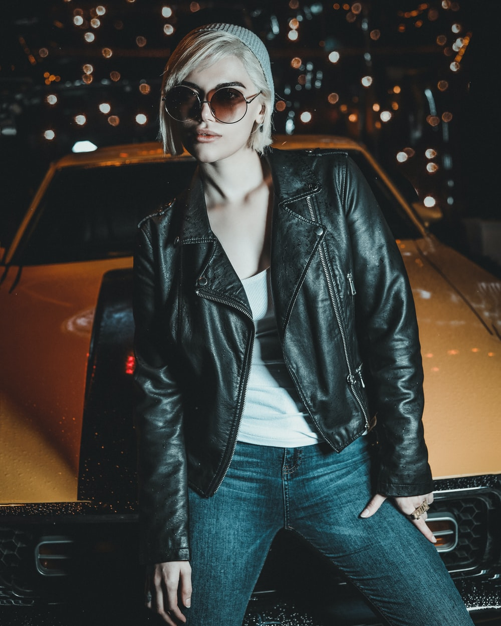 woman in black leather jacket and blue denim jeans wearing black sunglasses