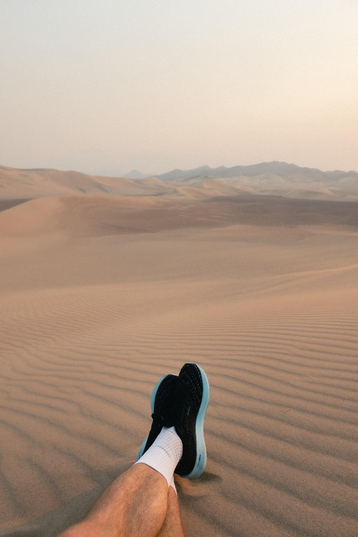 person in black pants walking on desert during daytime