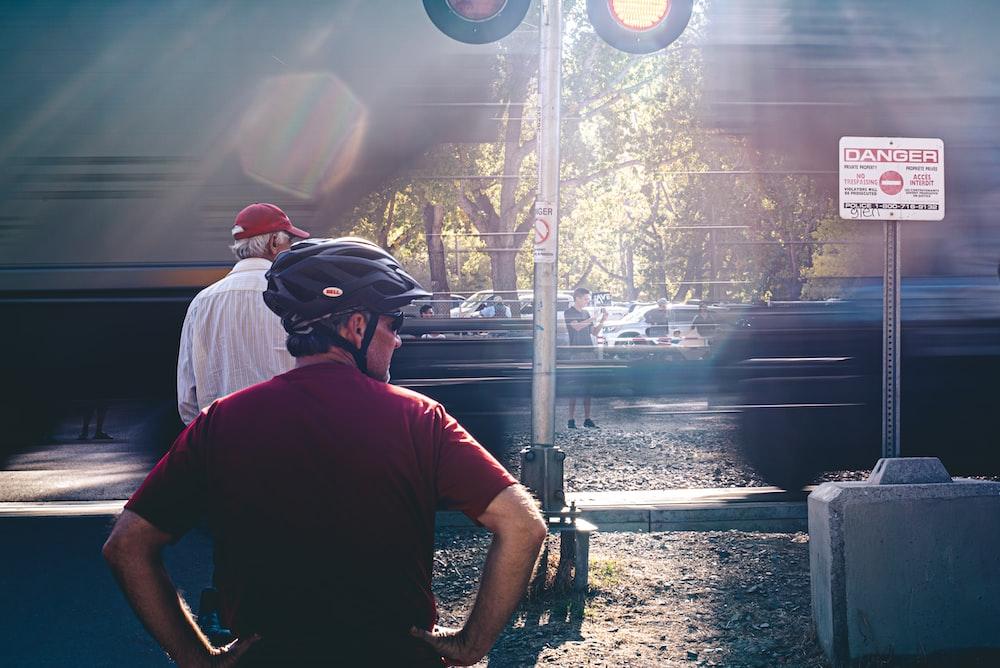 man in black crew neck t-shirt wearing black helmet standing near train rail during daytime