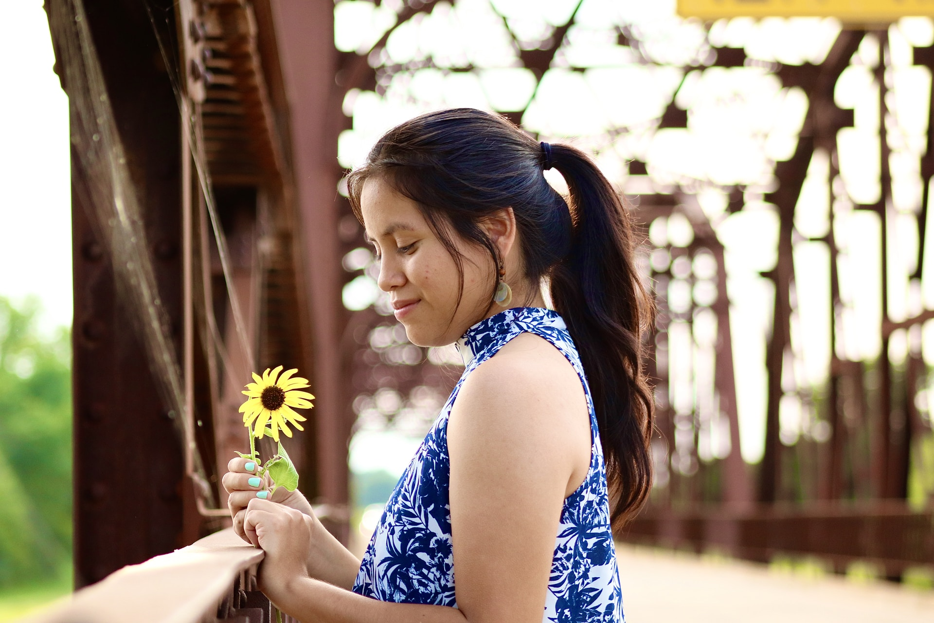 woman in blue and white floral sleeveless dress holding yellow flower during daytime