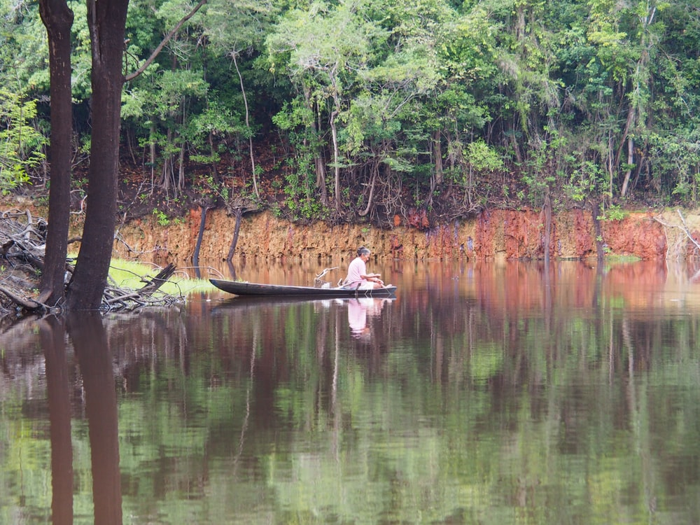 man in brown boat on lake during daytime