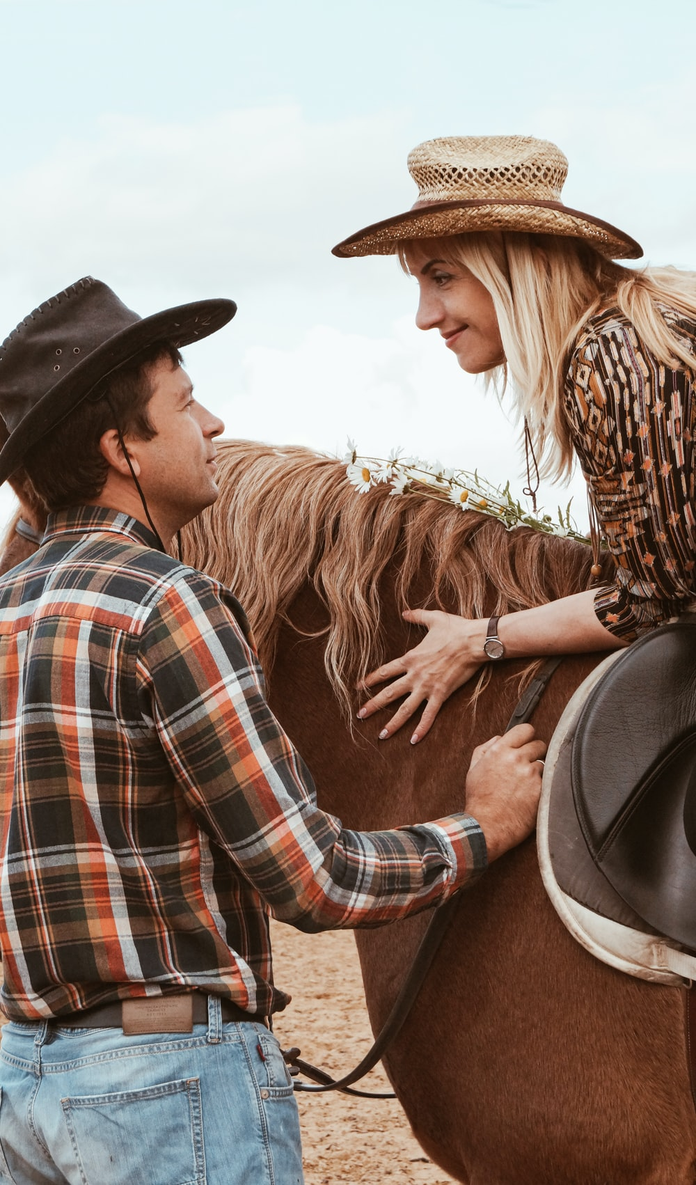 man in blue white and red plaid dress shirt and woman in brown cowboy hat