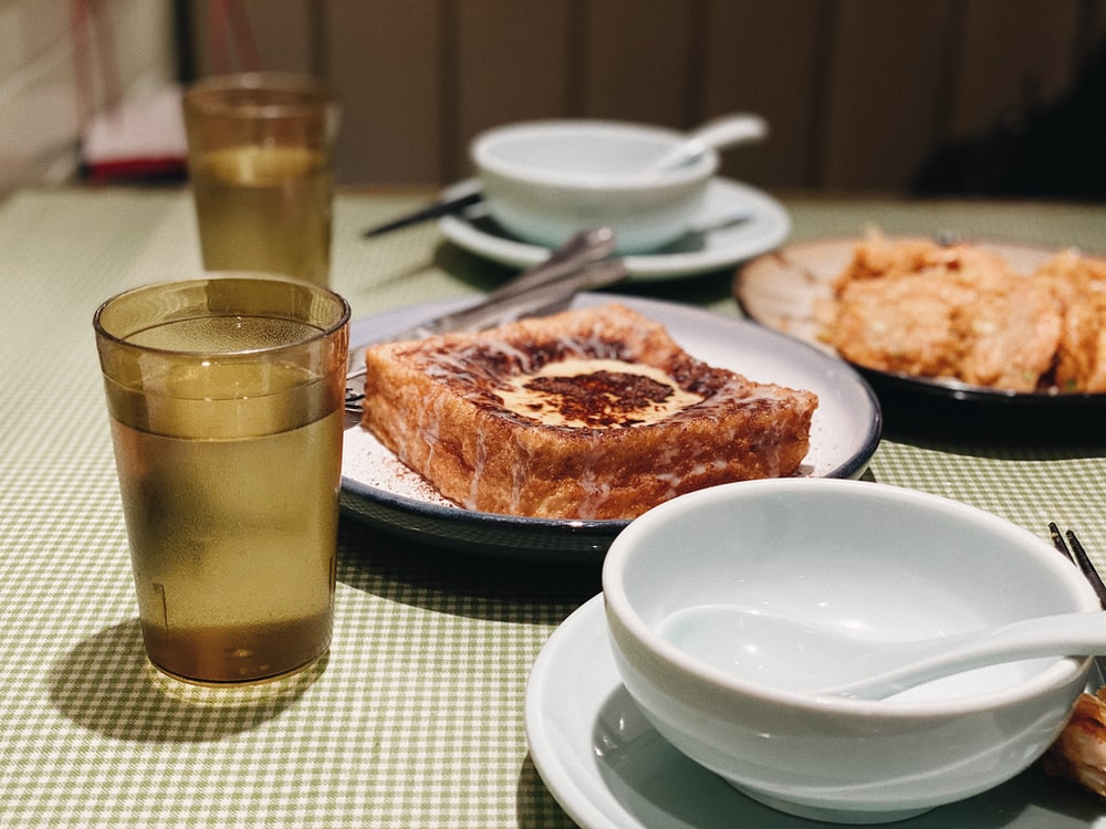 clear drinking glass beside white ceramic plate with food