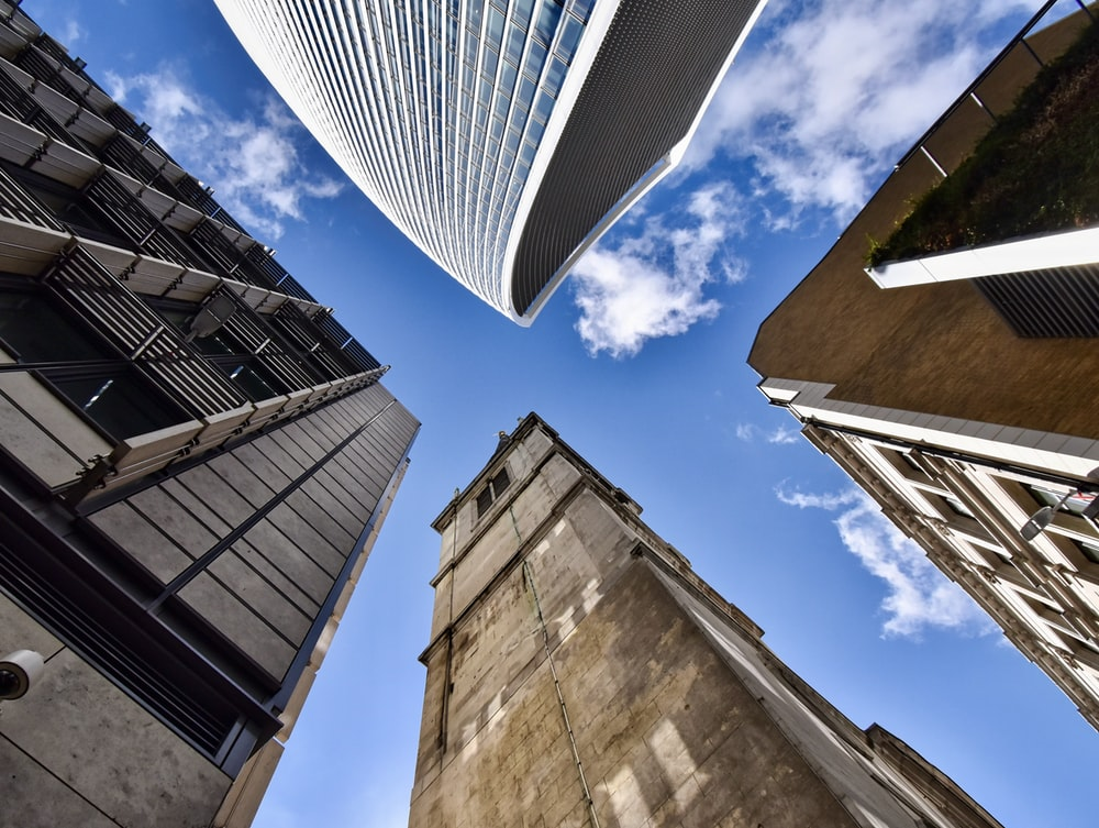 worms eye view of brown concrete building under blue and white sunny cloudy sky during