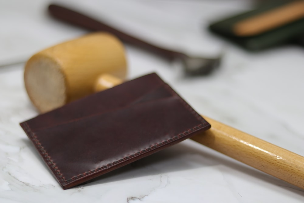 brown leather bifold wallet on white printer paper