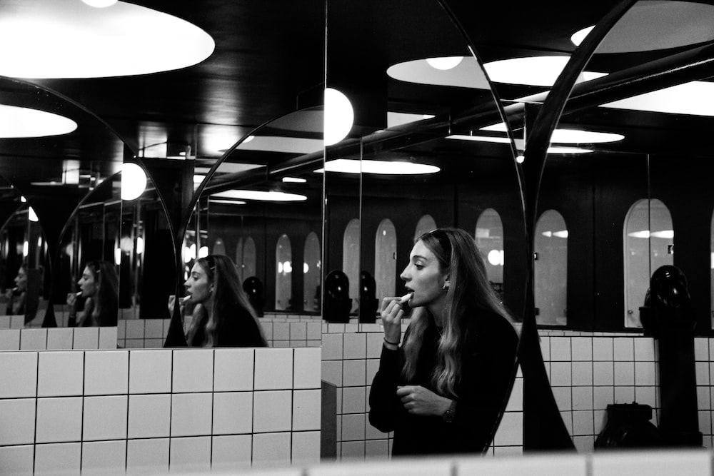 grayscale photo of woman in black coat standing in train station