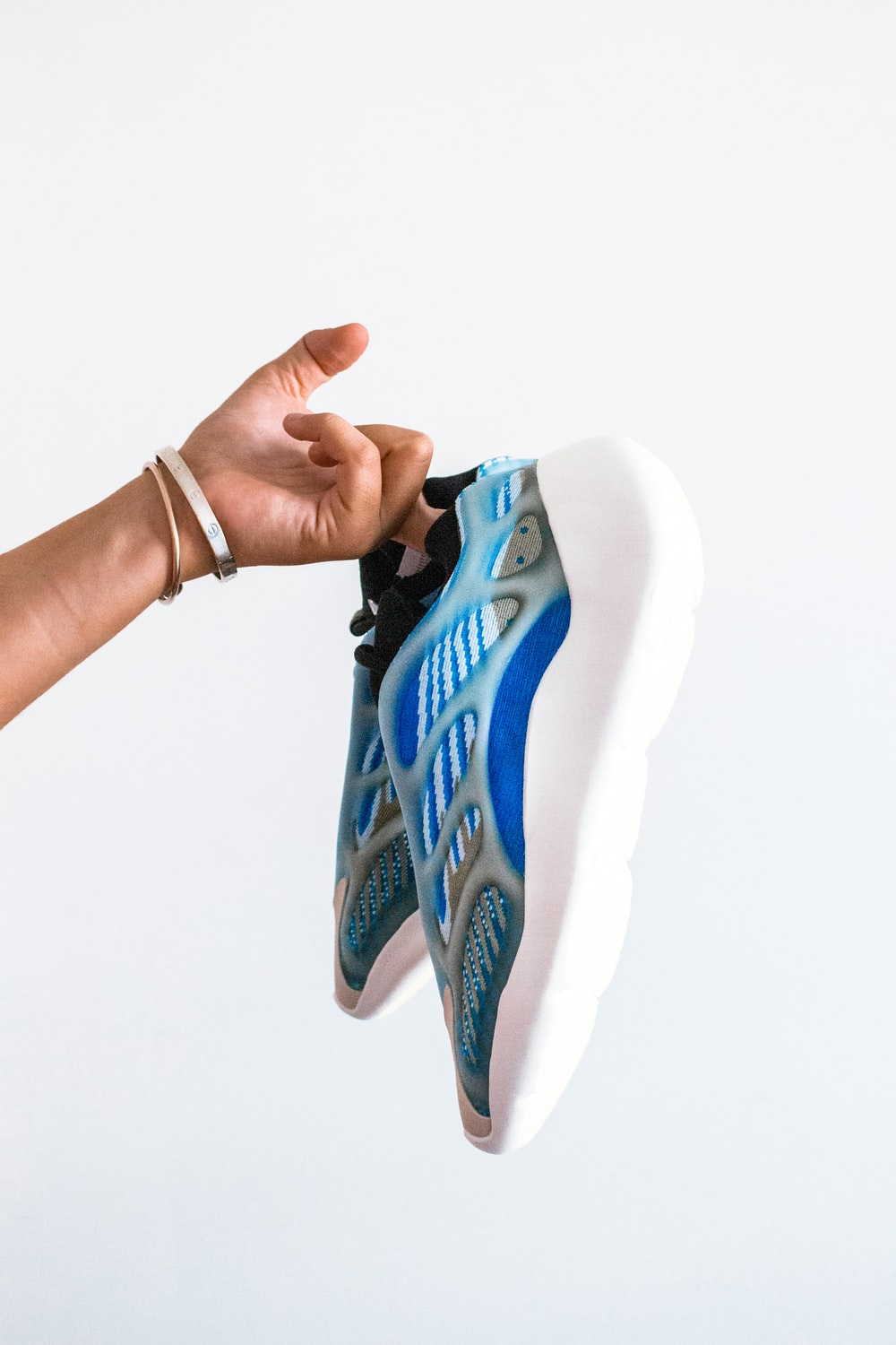 person holding white and blue nike shoe
