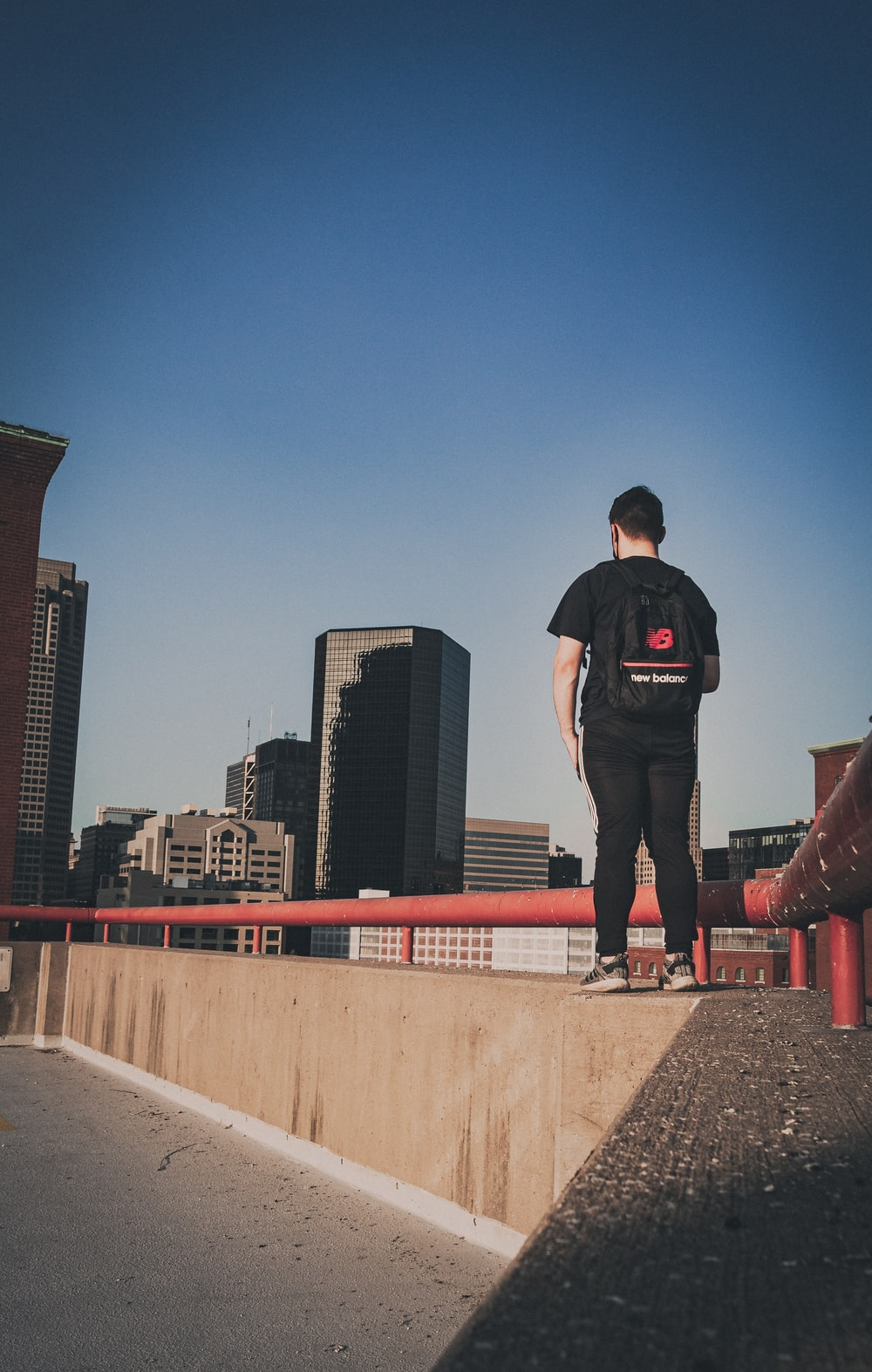 man in black t-shirt and black pants standing on concrete wall during daytime
