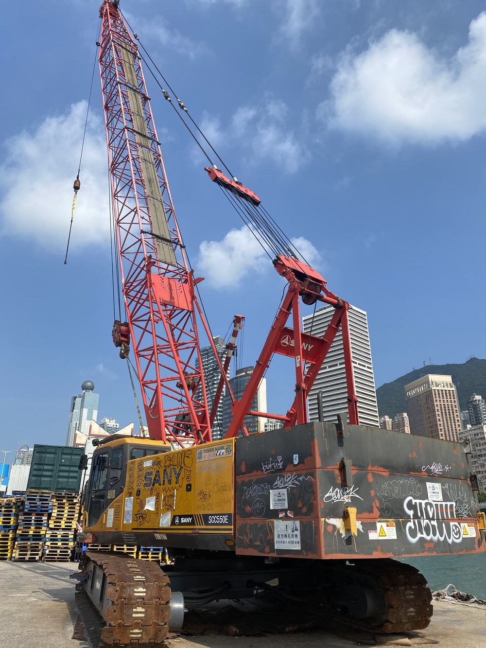 red and yellow crane near buildings during daytime