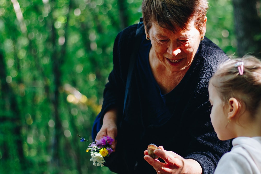 woman in black long sleeve shirt holding purple flower
