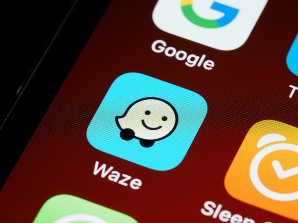 smartphone with the logo of Waze, a digital product that uses personalisation of sound design.