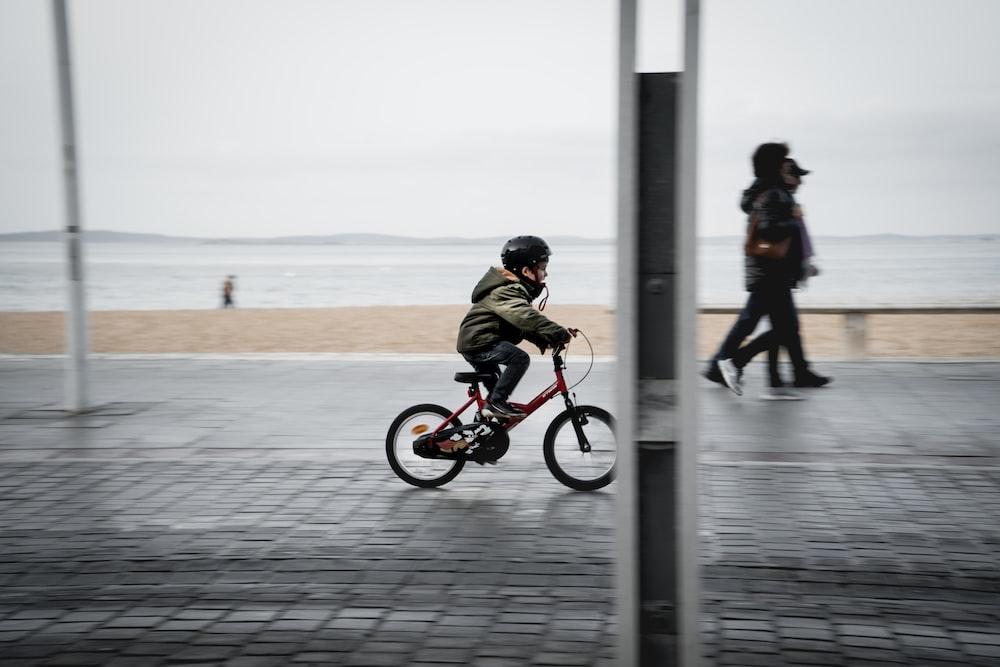 man in black jacket riding on red bicycle during daytime
