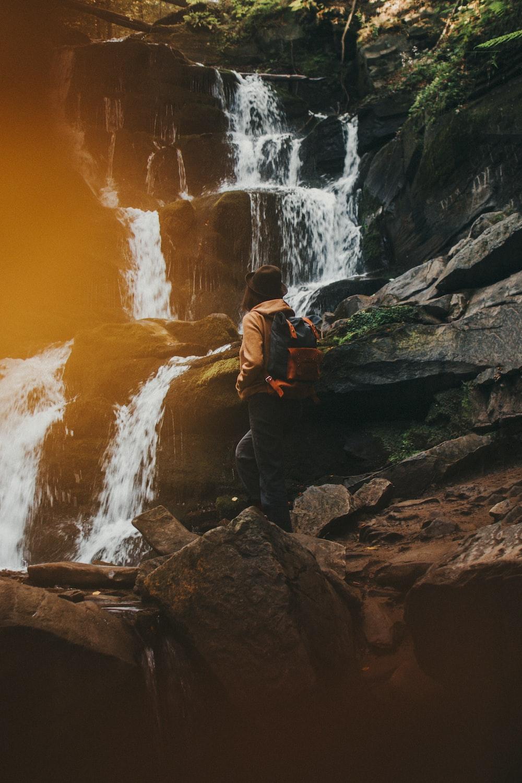 man in black jacket and orange backpack standing on rock near waterfalls during daytime