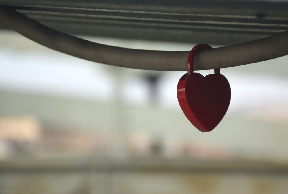 red heart hanging on black metal bar