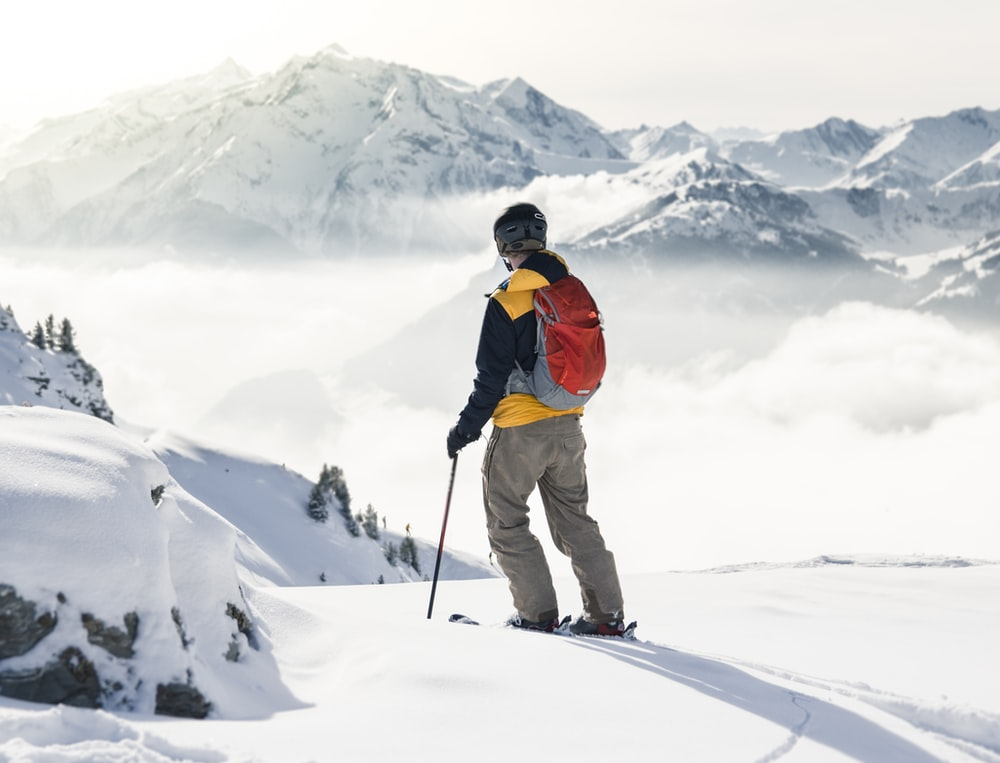 man in orange jacket and brown pants standing on snow covered mountain during daytime