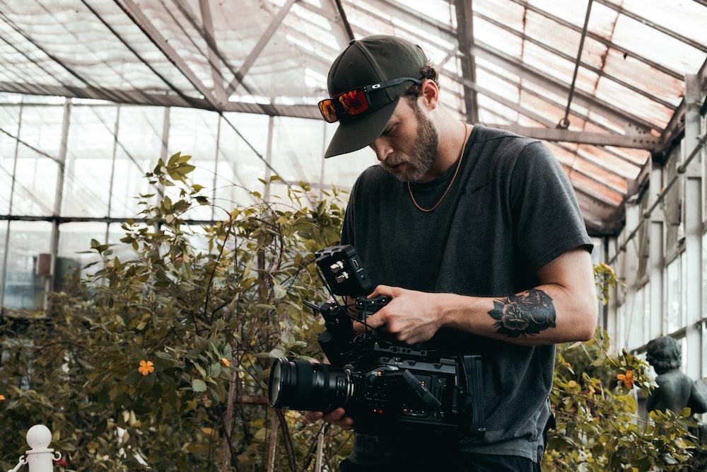 man in black crew neck t-shirt holding black dslr camera