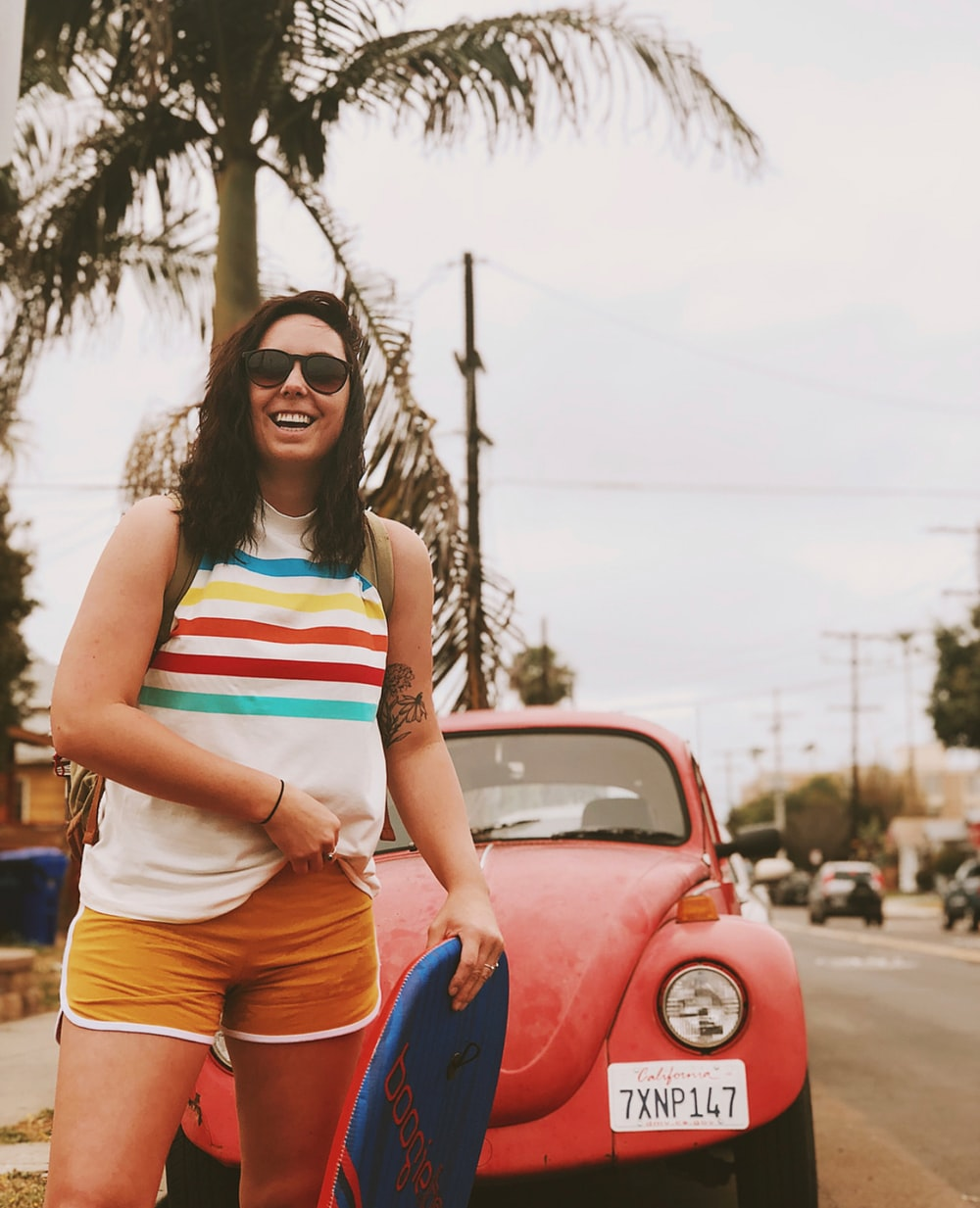 woman in white and pink stripe tank top and blue denim shorts standing on road during