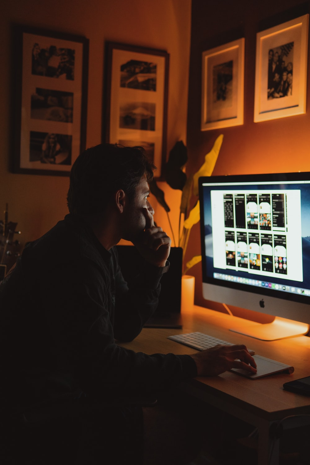 man in black jacket sitting in front of silver imac
