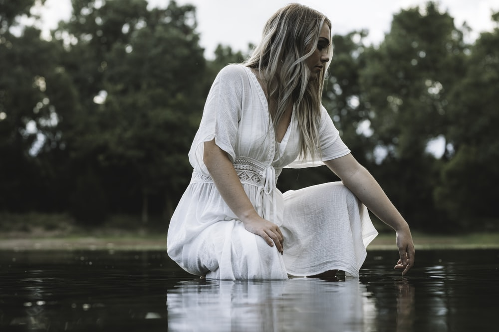 woman in white dress sitting on water during daytime