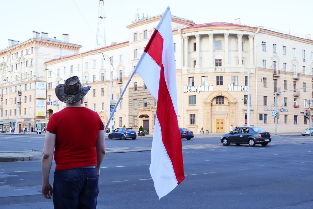 man in red t-shirt holding flag of us a during daytime