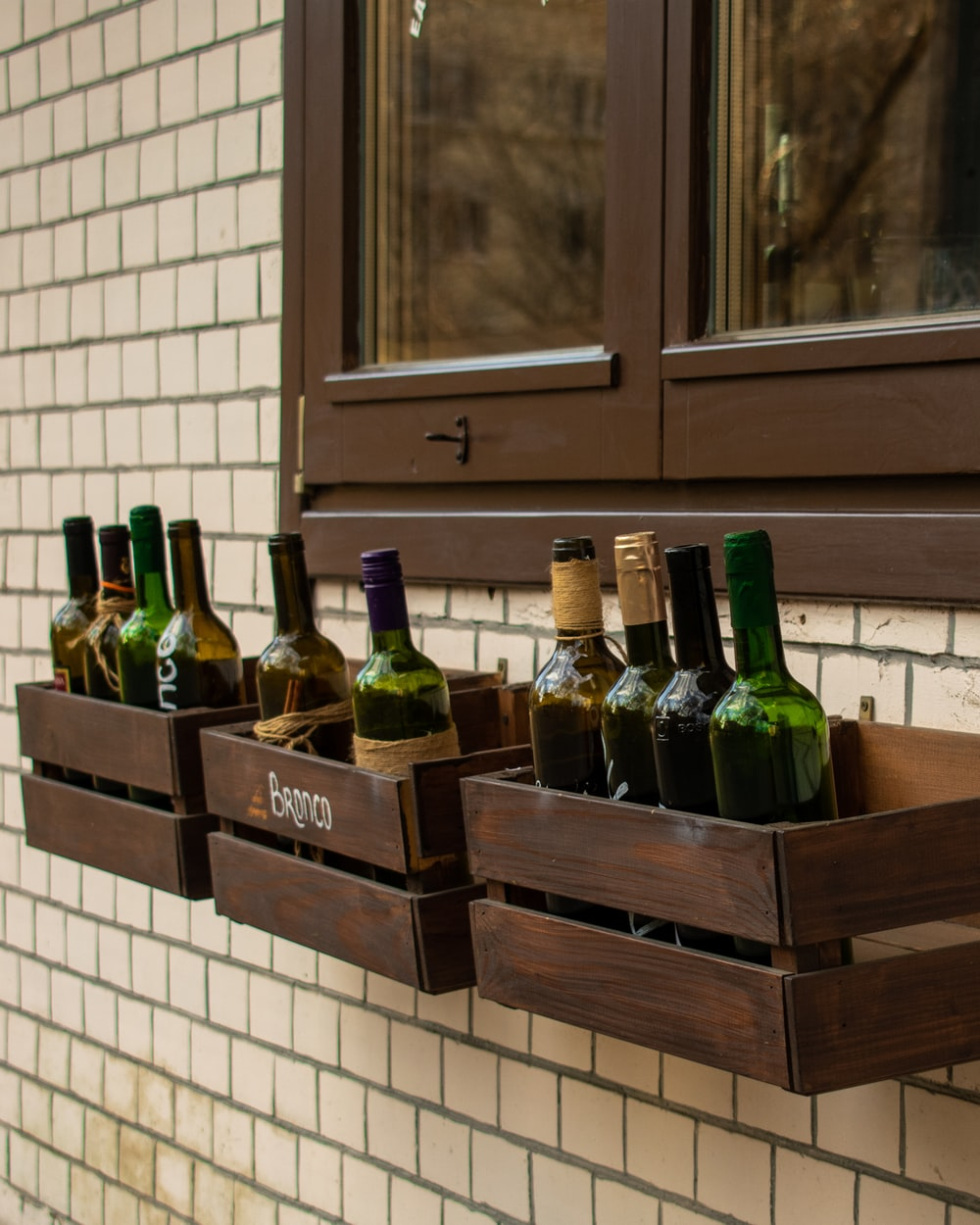 green glass bottles on brown wooden shelf