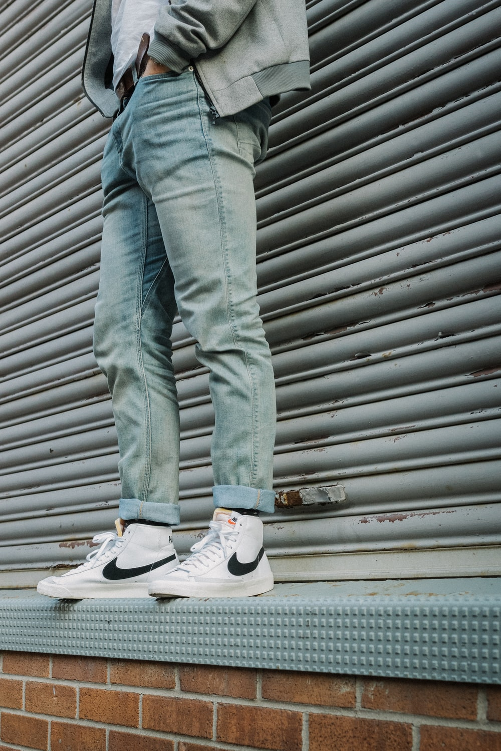 person in gray denim jeans and gray nike sneakers